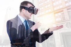 Pleasant businessman being about to touch virtual object on palm. Gentleness of touch. Cheerful bristled young man in a VR headset stretching out his hand to Royalty Free Stock Photo
