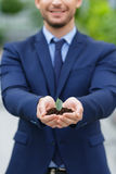 Pleasant businessman holding ground in hands Royalty Free Stock Image
