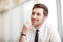 Pleasant businessman listening to music. Feel the rhythm. Pleasant handsome man holding headphones and listening to music while expressing gladness stock image