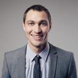 Pleasant businessman portrait on gray background Stock Image