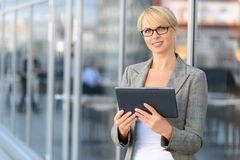 Pleasant businesswoman standing near office Royalty Free Stock Images