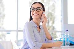 Pleasant businesswoman talking on mobile phone stock photo