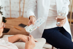 Pleasant caring nurse giving pills to an elderly woman Royalty Free Stock Photo