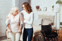 Pleasant caring woman helping with rehabilitation her disabled grandmother. I will help you. Positive aged disabled women waling with crutches while her caring Stock Photography