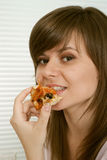 Pleasant Caucasian female eats pizza while sitting Royalty Free Stock Photos