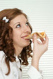 Pleasant Caucasian woman eats pizza while sitting Stock Photo