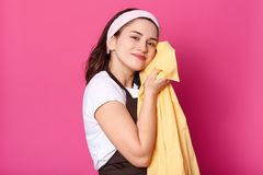 Pleasant charismatic female standing isolated over pink background in studio, wearing brown apron, white t shirt and headband,. Pressing yellow shirt to her stock photos