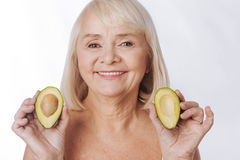 Pleasant charming woman having two avocado halves in her hands. Fruits in cosmetic industry. Pleasant charming senior woman holding two avocado halves and Stock Photography