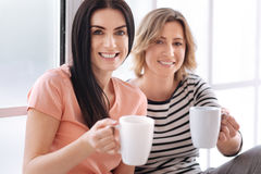 Pleasant charming women inviting you for a coffee Stock Image