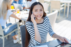 Female student having phone conversation outdoors. Pleasant chat. Cheerful university lady looking at the sky while listening to her groupmate talking on a Royalty Free Stock Photos