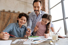 Pleasant cheerful family doing watercolor brush strokes Stock Image