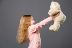 Pleasant cheerful girl looking at her bear stock photography