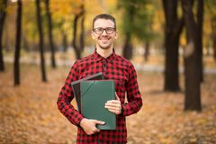 Pleasant cheerful handsome realtor holding folder and expressing positivity while standing in autumn park. Ready to sale stock photography