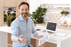 Pleasant cheerful man holding a printout. Sharing ideas. Upbeat young man sitting next to the kitchen counter, holding a printout and reaching out a hand to the royalty free stock photo