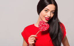 Pleasant cheerful woman holding lollypop Stock Image