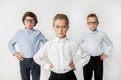 Pleasant clever kids are expressing sureness. Professional smart team concept. Portrait of serious intelligent children are standing with arms akimbo and looking Stock Images