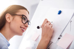Pleasant colleagues discussing project. Write it down. Positive delighted smiling woman holding pen and making notes on the board while expressing gladness royalty free stock images