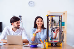 Pleasant colleagues sitting at the table. Nice device. Cheerful delighted smiling colleagues sitting at the table and using 3d printer while expressing gladness royalty free stock photography