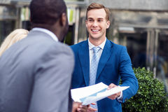 Pleasant colleagues working with papers. Here you are. Pleasant cheerful colleagues holding papers and standing near office building while expressing gladness royalty free stock image
