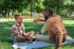 Delighted nice man telling a story to his son. Pleasant communication. Delighted nice men smiling to his son while telling him a story stock images