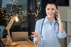 Nice female doctor talking on the phone royalty free stock photography