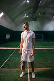 Pleasant confident tennis player standing in the indoor court Royalty Free Stock Image
