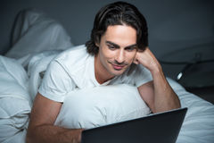 Pleasant content man using laptop in bed Stock Images