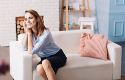 Pleasant content woman sitting on the couch Stock Image