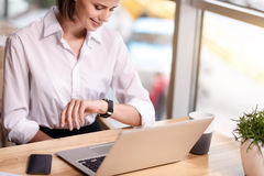 Pleasant content woman sitting at the table. Mind the time. Pleasant content beautiful woman sitting at the table and looking at her wrist watch while expressing royalty free stock image