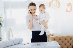 Charming young woman expressing gladness. Pleasant conversation. Joyful lady holding her child while having pleasant business talk royalty free stock photos