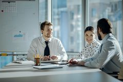 Joyful colleagues chatting cheerfully during meeting stock images