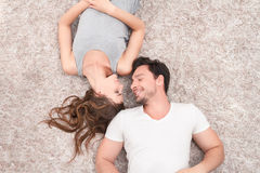 Pleasant couple lying on the carpet Stock Images