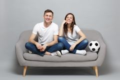Pleasant couple woman man football fans in white t-shirt cheer up support favorite team with soccer ball isolated on. Pleasant couple women men football fans in royalty free stock image