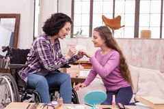 Pleasant crippled woman assisting girl with makeup. Tips for makeup. Attractive crippled women using cosmetics while speaking with daughter Stock Photography