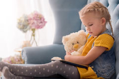 Pleasant cute girl looking at the tablet stock image