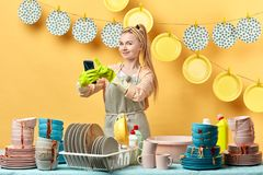 Pleasant cute housewife holding the mobile phone and making a phone call stock photos