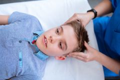 Pleasant cute young boy peacefully lying on the couch during massage royalty free stock photo