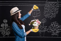 Pleasant delighted florist watering flowers Royalty Free Stock Photo