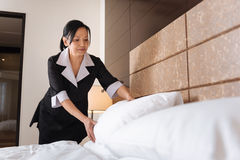 Pleasant delighted hotel maid making the bed. Part of my duties. Pleasant delighted Asian hotel maid standing over the bed and putting a pillow while making it Royalty Free Stock Images