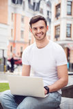 Pleasant delighted man using laptop. Express gladness. Cheerful delighted smiling man sitting outdoor and smiling while using laptop stock photography