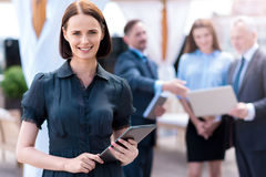 Pleasant delighted woman holding tablet. Confidence in mind. Positive beautiful smiling women holding tablet and expressing gladness while her colleagues stock photos