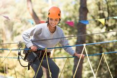 Pleasant delighted woman trying to keep the balance. On the high ropes route. Beautiful confident cheerful woman holding on to the ropes and looking down while Stock Image
