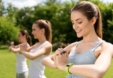 Pleasant delighted women doing sport exercises outdoors Royalty Free Stock Image