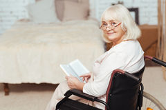 Pleasant disabled woman sittign in the wheelchair at home Royalty Free Stock Photography