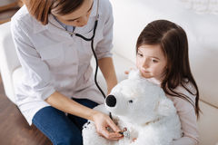 Pleasant doctor examining fluffy toy Stock Images