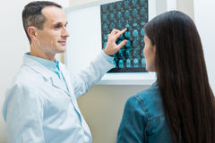 Pleasant doctor explaining the results of CT scan to patient. Detailed explanation. Pleasant male doctor pointing at the results of computer tomography while royalty free stock images