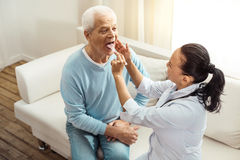 Pleasant elderly man doing a medical checkup. Importance of health. Pleasant delighted elderly men opening his mouth and allowing a doctor to look inside while royalty free stock image