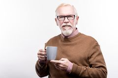 Pleasant elderly man in eyeglasses holding coffee cup. Delicious coffee. Handsome elderly man in eyeglasses holding a cup of coffee in one hand and supporting it Stock Photography