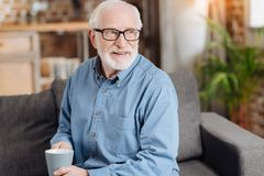Pleasant elderly man holding a cup of coffee. Favorite drink. Charming elderly man in eyeglasses sitting on the couch, holding a coffee cup and looking into the Stock Photography