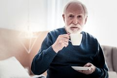 Pleasant elderly man holding a cup of tea. Favourite drink. Pleasant nice elderly man holding a cup an drinking tea while looking at you Royalty Free Stock Images